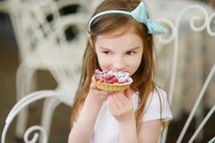 Adorable little girl eating fresh strawberry cake Stock Images