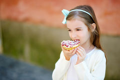 Adorable little girl eating fresh sweet strawberry cake outdoors on warm and sunny summer day Royalty Free Stock Photo