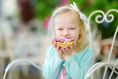 Adorable little girl eating fresh sweet strawberry cake outdoors on warm and sunny summer day Royalty Free Stock Images