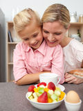 Adorable little girl eating fruit with her mother Royalty Free Stock Photography