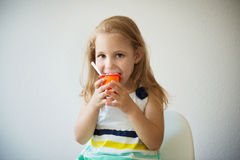 Adorable little girl eating fruit yogurt at home Royalty Free Stock Images