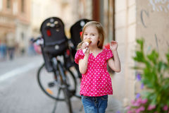 Adorable little girl eating ice-cream outdoors Stock Image