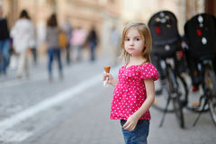 Adorable little girl eating ice-cream outdoors Royalty Free Stock Photography