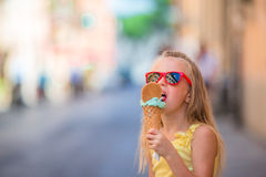 Adorable little girl eating ice-cream outdoors at summer. Cute kid enjoying real italian gelato near Gelateria in Rome Royalty Free Stock Photography