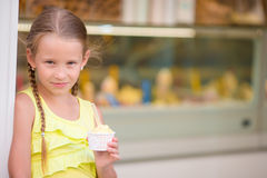 Adorable little girl eating ice-cream outdoors at summer. Cute kid enjoying real italian gelato near Gelateria in Rome Stock Photography