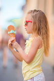 Adorable little girl eating ice-cream outdoors at summer. Cute kid enjoying real italian gelato near Gelateria in Rome Stock Photos