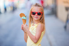 Adorable little girl eating ice-cream outdoors at summer. Cute kid enjoying real italian gelato near Gelateria in Rome Stock Photo