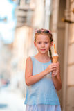 Adorable little girl eating ice-cream outdoors at summer. Cute kid enjoying real italian gelato near Gelateria in Rome Stock Image
