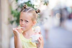 Adorable little girl eating ice-cream outdoors at summer. Cute kid enjoying real italian gelato near Gelateria in Rome. Adorable little girl eating ice-cream Royalty Free Stock Photography
