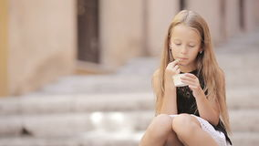 Adorable little girl eating ice-cream outdoors at summer. Cute kid enjoying real italian gelato in Rome stock video