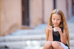 Adorable little girl eating ice-cream outdoors at summer. Cute kid enjoying real italian gelato in Rome. Adorable little girl eating ice-cream outdoors at summer Royalty Free Stock Photos