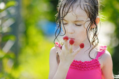 Adorable little girl eating raspberries. Off her fingers Stock Photography