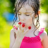 Adorable little girl eating raspberries Royalty Free Stock Images