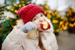 Adorable little girl eating red apple covered with sugar icing on traditional Christmas market. Stock Photography