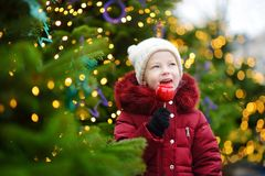 Adorable little girl eating red apple covered with sugar icing on traditional Christmas market. Stock Images