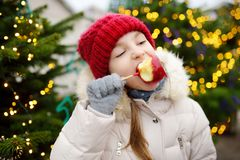 Adorable little girl eating red apple covered with sugar icing on traditional Christmas market. Stock Image
