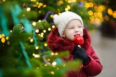 Adorable little girl eating red apple covered with sugar icing on traditional Christmas market. Royalty Free Stock Images