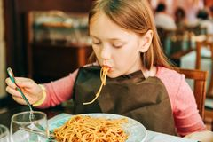 Adorable little girl eating spaghetti with bolognese sauce Stock Photo