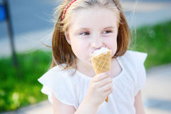Adorable little girl eating tasty ice cream at park. On warm sunny summer day Royalty Free Stock Photo