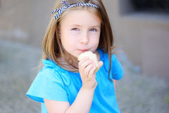 Adorable little girl eating tasty ice cream at park on warm sunny summer day stock image
