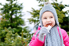 Adorable little girl eating warm waffle on cold winter day Stock Photos