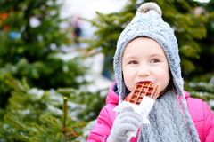 Adorable little girl eating warm waffle on cold winter day Royalty Free Stock Images