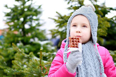 Adorable little girl eating warm waffle on cold winter day Royalty Free Stock Image