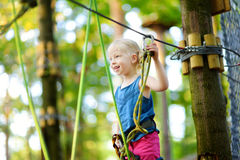 Adorable little girl enjoying her time in climbing adventure park on warm and sunny summer day Stock Images