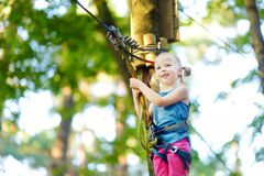 Adorable little girl enjoying her time in climbing adventure park on warm and sunny summer day Stock Image