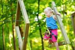Adorable little girl enjoying her time in climbing adventure park on warm and sunny summer day Royalty Free Stock Photo