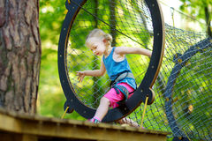 Adorable little girl enjoying her time in climbing adventure park on warm and sunny summer day Royalty Free Stock Images