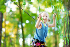 Adorable little girl enjoying her time in climbing adventure park on warm and sunny summer day Stock Photography