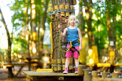 Adorable little girl enjoying her time in climbing adventure park on warm and sunny summer day Stock Photos