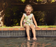 Adorable little girl enjoying sitting by edge of pool Royalty Free Stock Photography