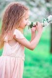 Adorable little girl enjoying smell in a flowering cherry spring garden Royalty Free Stock Photos