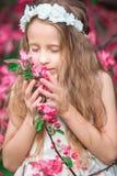 Adorable little girl enjoying smell in a flowering spring garden Royalty Free Stock Image