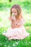 Adorable little girl enjoying smell in a flowering spring garden Stock Photo