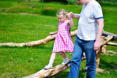 Adorable little girl with father holding her hand walking on wood on sunny summer day. Adorable little girl with father holding her hand walking on wood on royalty free stock photos