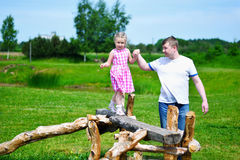 Adorable little girl with father holding her hand walking on wood on sunny summer day. Adorable little girl with father holding her hand walking on wood on stock photography