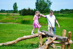 Adorable little girl with father holding her hand walking on wood on sunny summer day.  royalty free stock photos