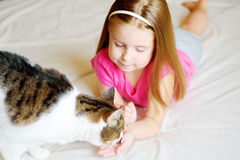 Adorable little girl feeding her cat. At bed Royalty Free Stock Photos