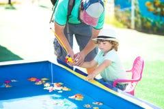 Adorable little girl fishing. stock photos