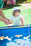 Adorable little girl fishing with her father. stock images