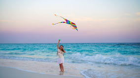 Adorable little girl with flying kite on tropical beach at sunset. Kids play on ocean shore. Child with beach toys. Little girl flying a kite on beach at sunset stock video