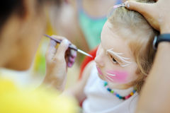Adorable girl getting her face painted Stock Photos