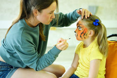 Adorable little girl getting her face painted like tiger by artist Royalty Free Stock Photos