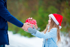 Adorable little girl giving christmas box gift in winter outdoors Royalty Free Stock Image