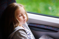 Adorable little girl going on vacations and traveling by railway. Adorable little girl going on vacations and traveling by railway Royalty Free Stock Images
