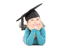 Adorable little girl with graduation hat laying down and daydrea Royalty Free Stock Photography