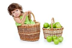 Adorable little girl with green apples in basket Royalty Free Stock Photos